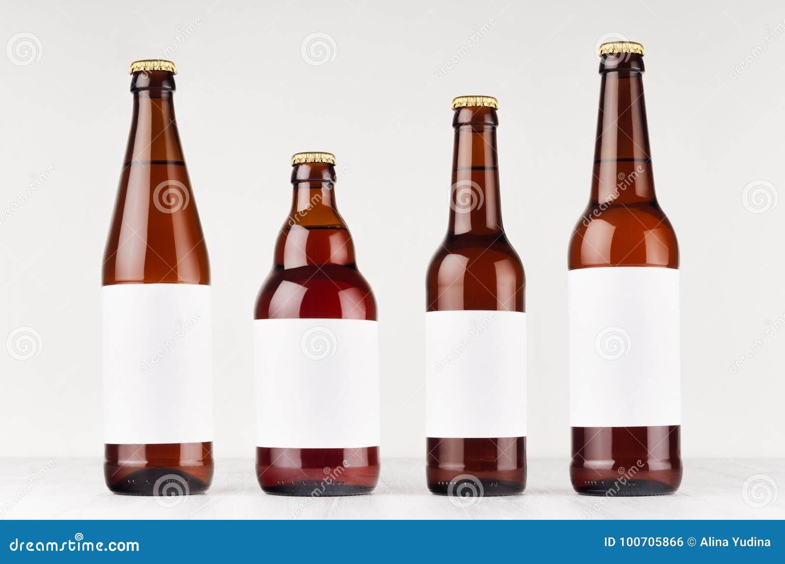 Tipo de la colección de las botellas de cerveza de Brown diverso con la etiqueta blanca en blanco en el tablero de madera blanco,