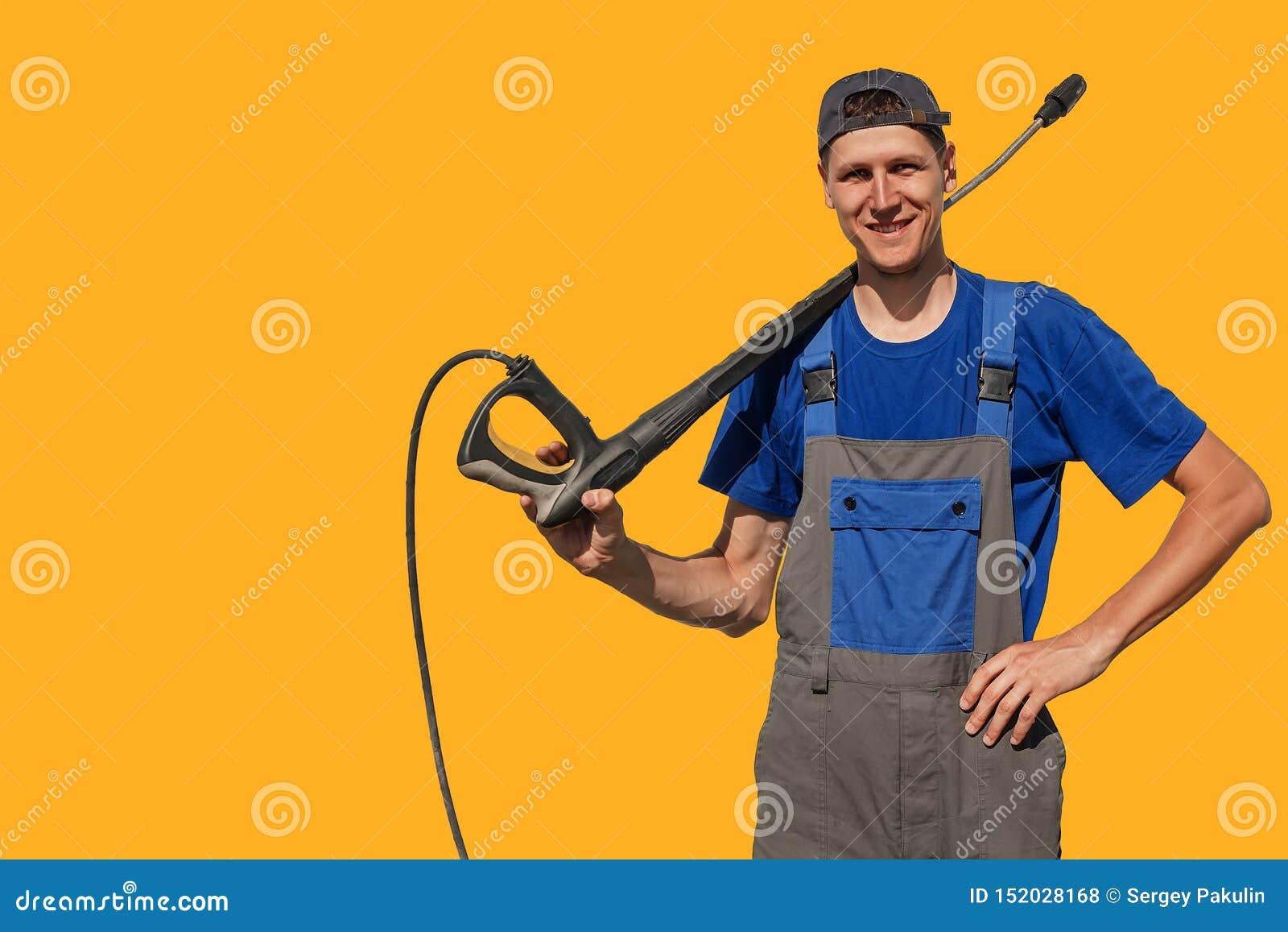 Tipo esile alto con una pistola per un autolavaggio isolato su fondo giallo Un lavoratore in tute esamina la macchina fotografica