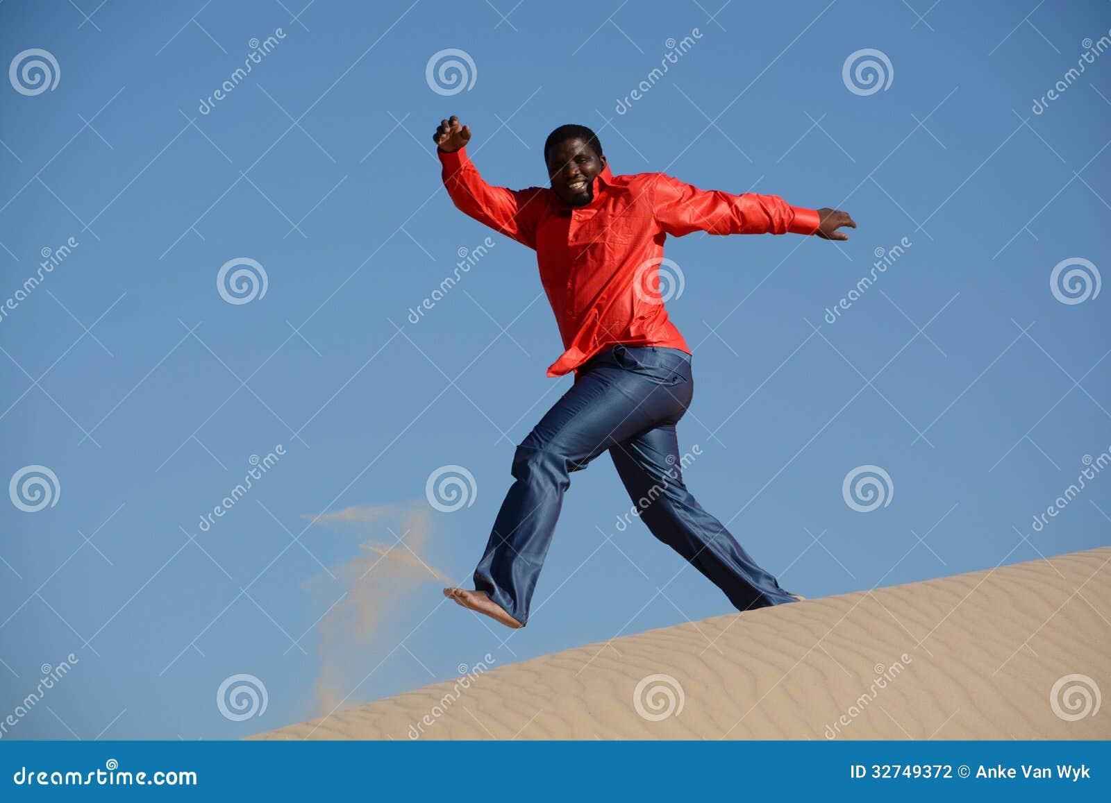 Tipo felice che corre giù la duna