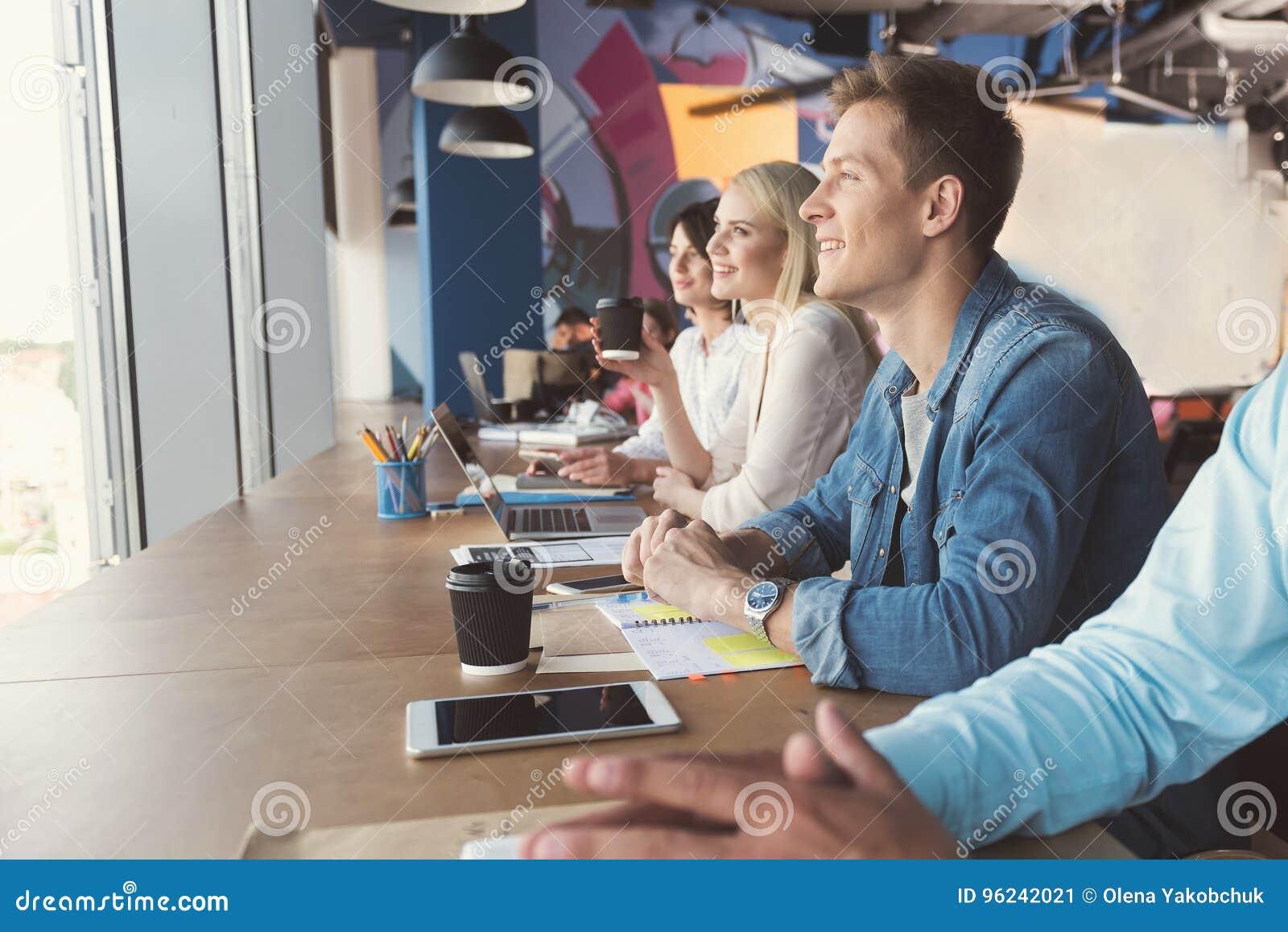 Tipo felice e ragazze giovanili che comunicano sul lavoro in ufficio