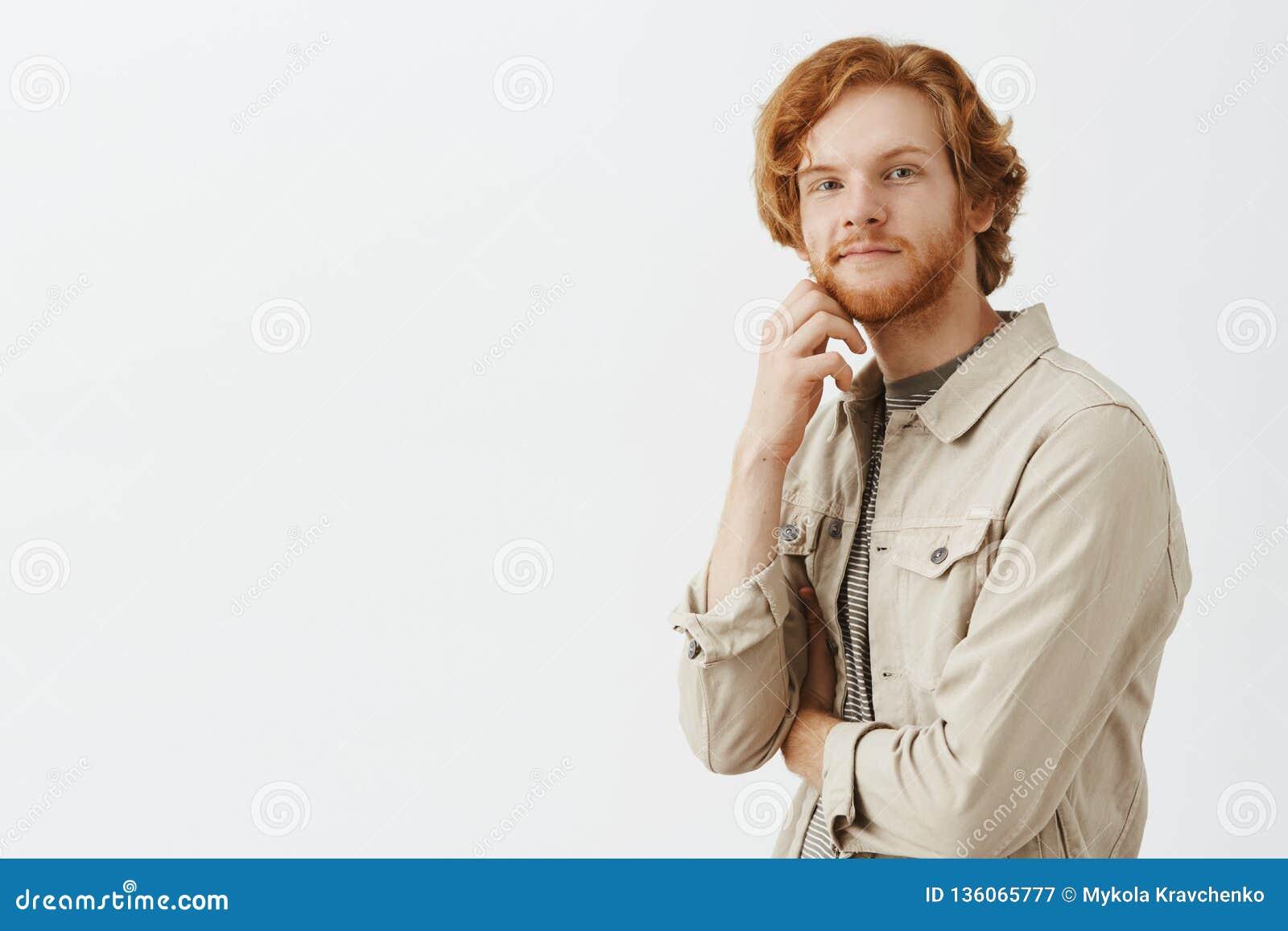 Tipo gentile amichevole e rilassato curioso della testarossa con la mano della tenuta dei capelli ondulati e della barba sulla co