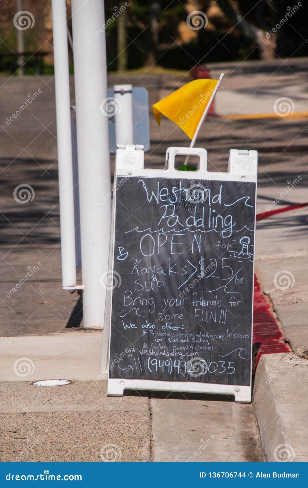 Tipo placa de calle del tablero de bocadillo que hace publicidad de un batimiento y de un negocio de alquiler del kajak
