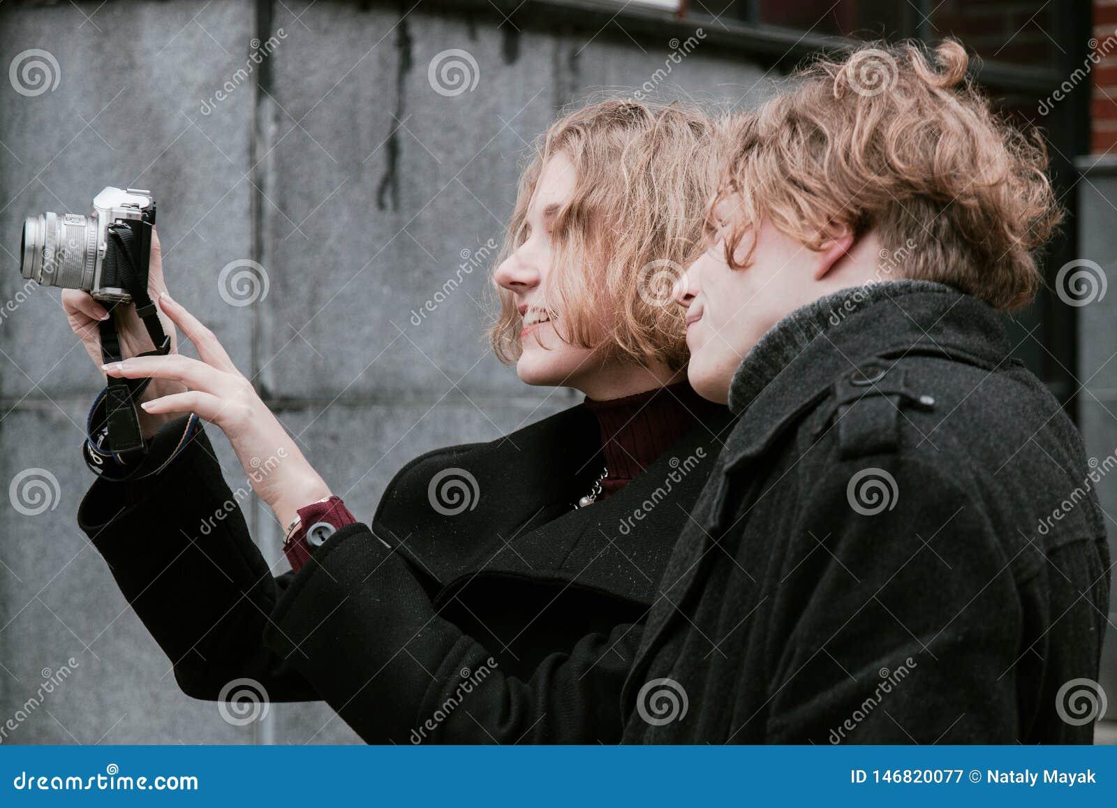 Tipo riccio-dai capelli biondo e la stessa ragazza prendere le immagini se stessi e prendere le immagini intorno