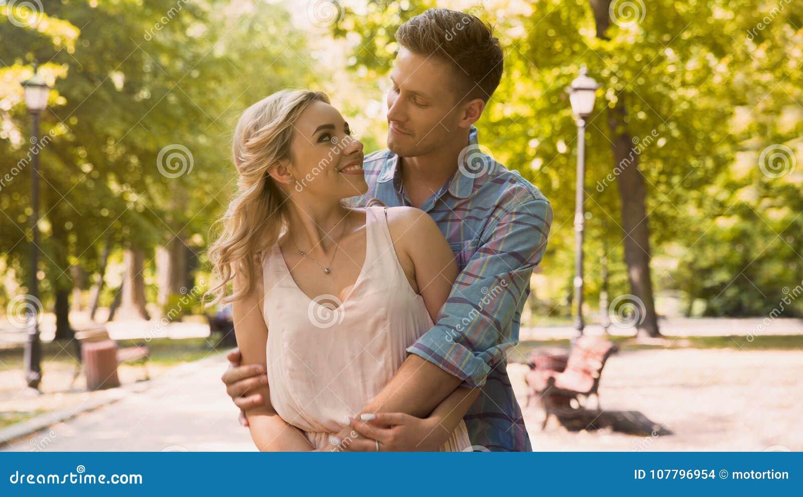 Tipo sveglio e ragazza che se esaminano tenero con amore, stringendo a sé nel parco