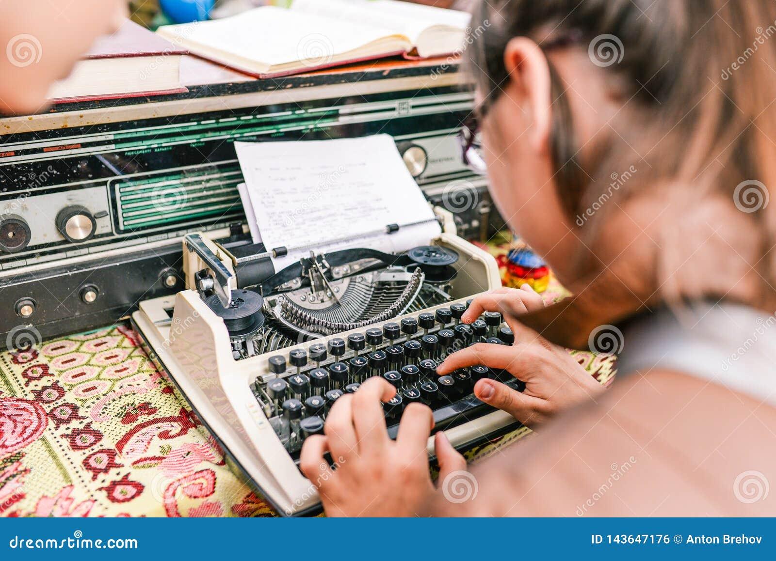 Tipos de la chica joven en una máquina de escribir El periodista imprime noticias Concepto o noticias del negocio