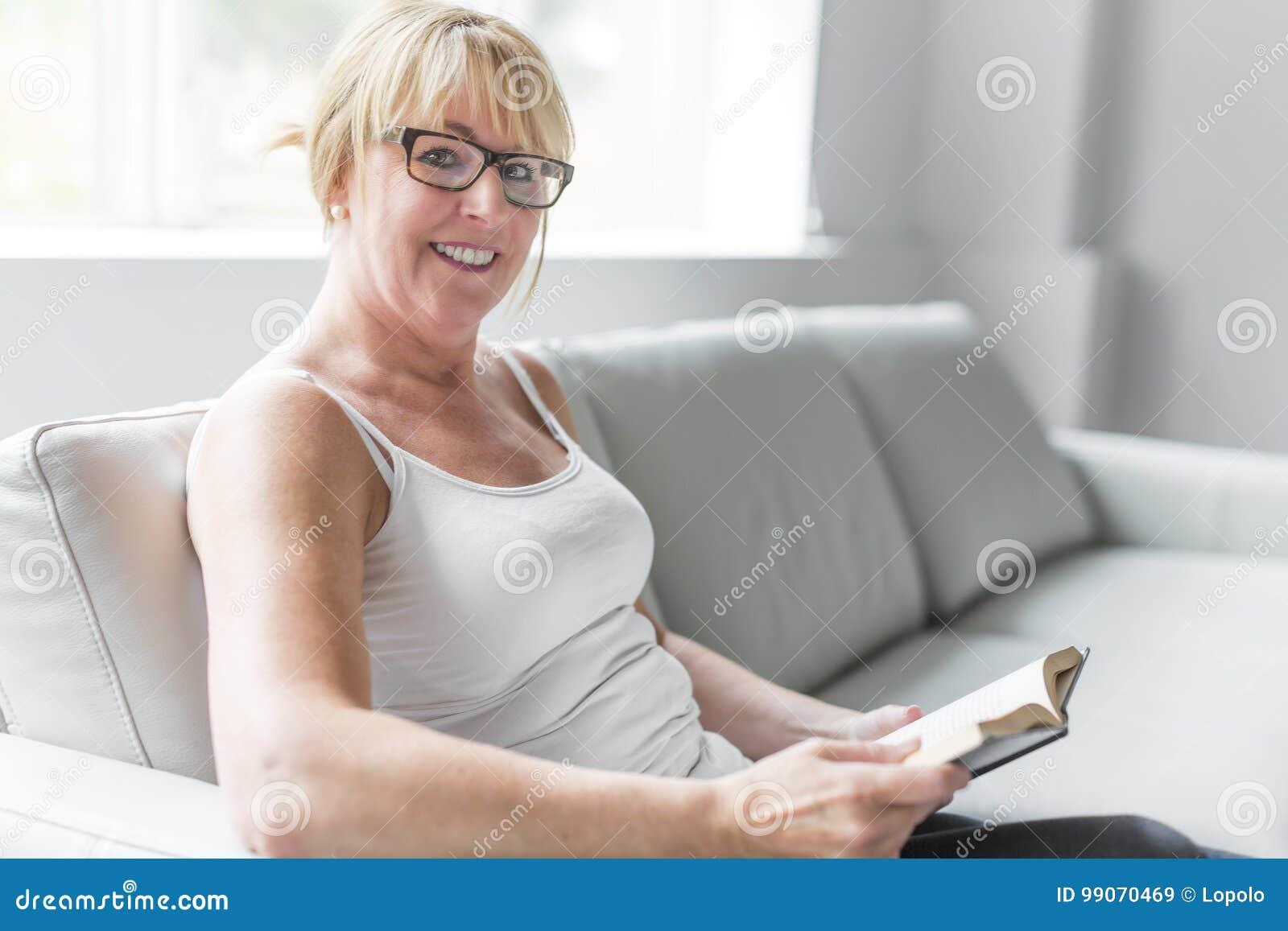 Tir d 39 une femme m re lisant son roman pr f r tandis qu 39 la maison dans le salon image stock - Regarder 7 a la maison gratuitement ...