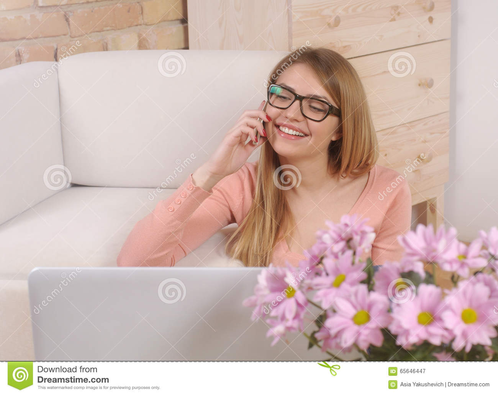 Tiré d une jeune femme faisant un appel téléphonique et à l aide de son ordinateur portable a