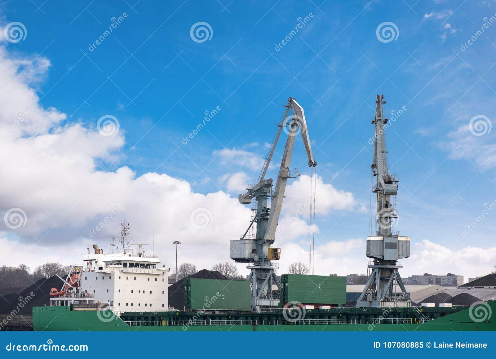 Tiré de deux vieux, le port rouillé et gris tend le cou avec de grands crochets, soulevant la cargaison dans le bateau sur le fon