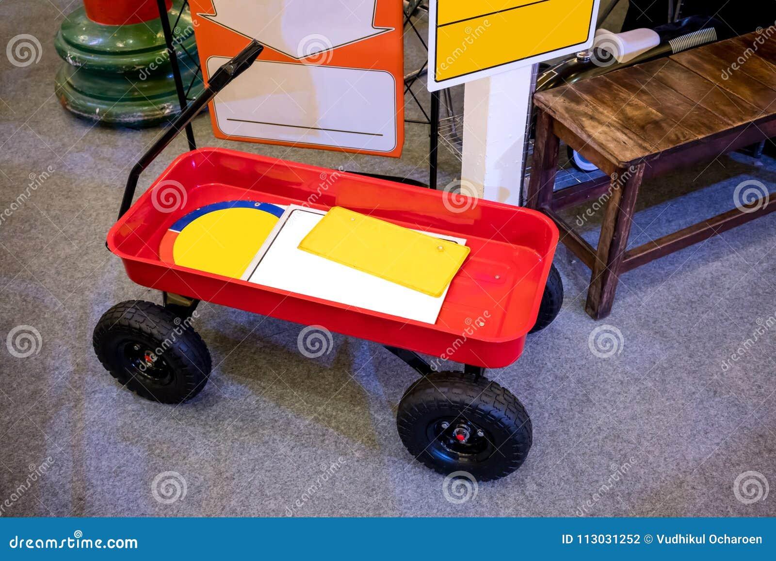 Tirón rojo a lo largo del carro del carro con la manija negra y las ruedas parqueadas