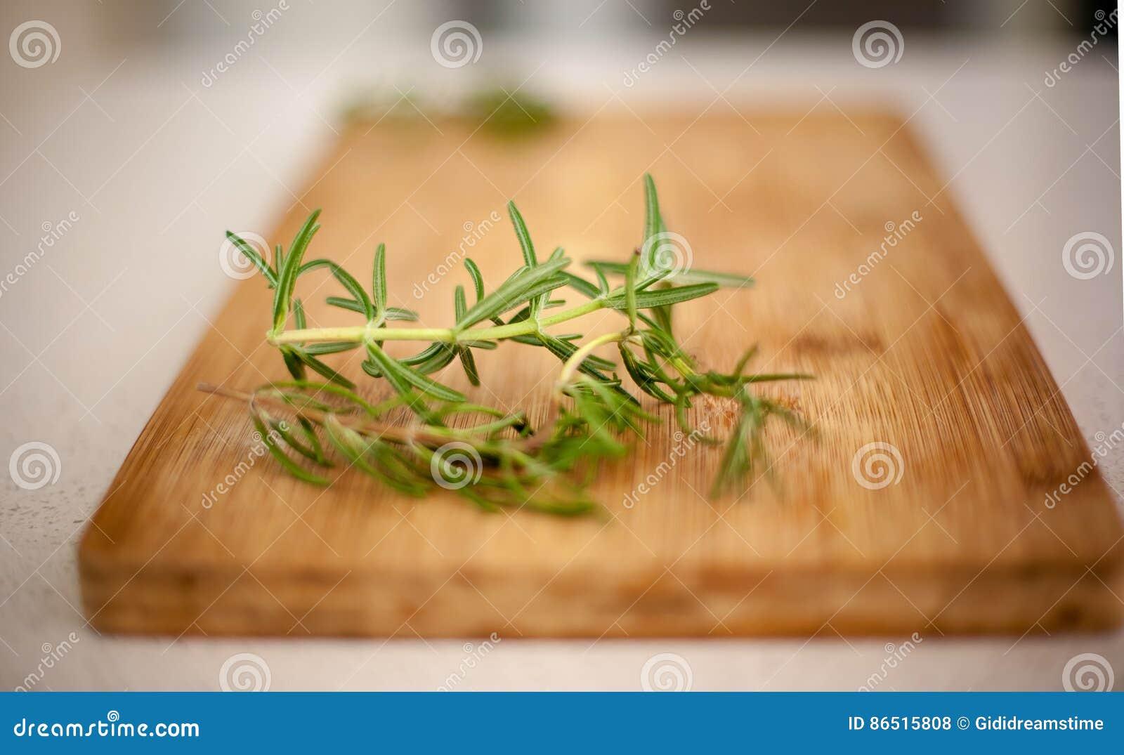 Tir brouillé de romarin et de thym sur la planche à découper en bois, copie