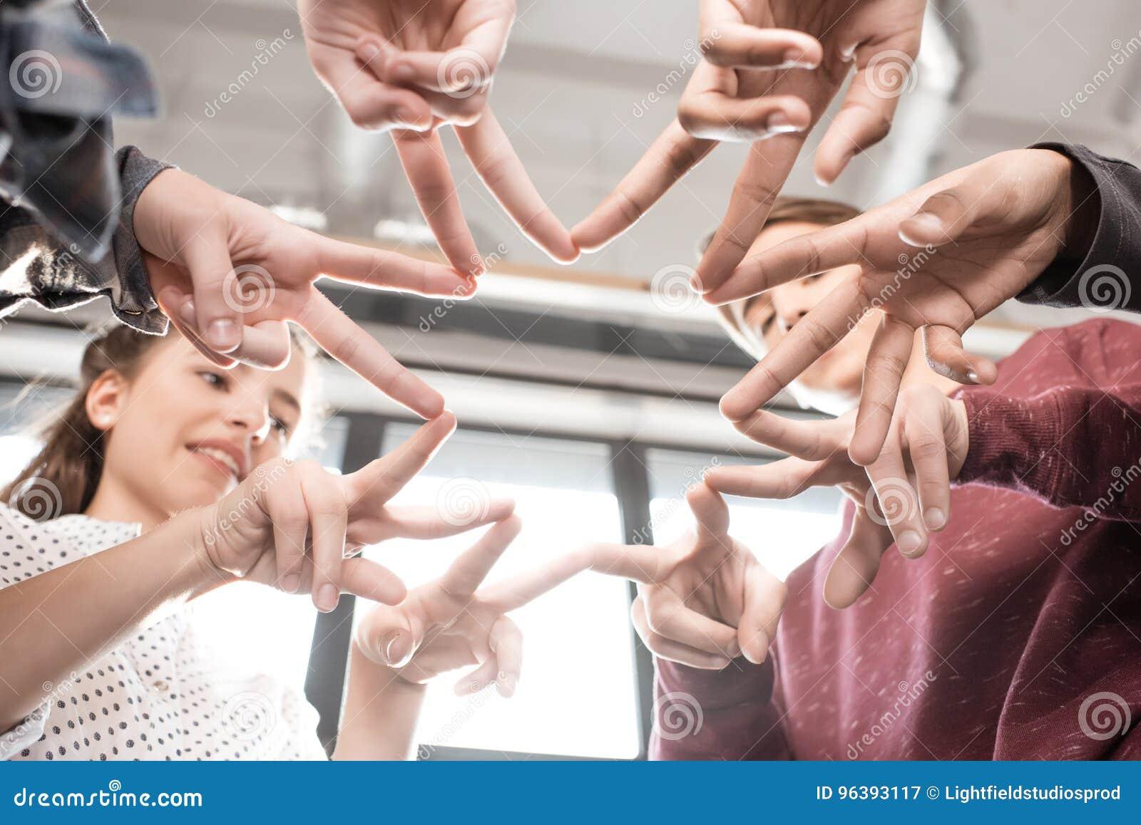 Tir cultivé des adolescents faisant des gestes avec des doigts ensemble à l intérieur