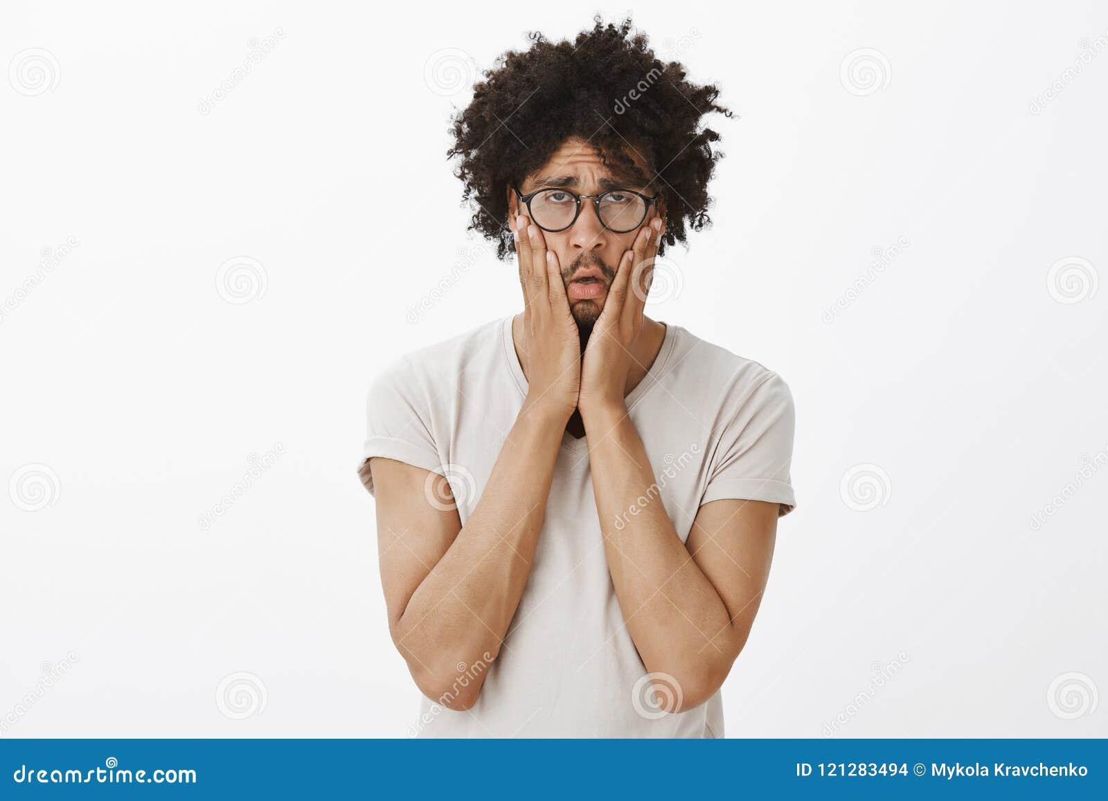 Tir de studio de type mignon épuisé et ennuyé sombre avec la coupe de cheveux Afro en verres, serrant des joues avec des paumes e