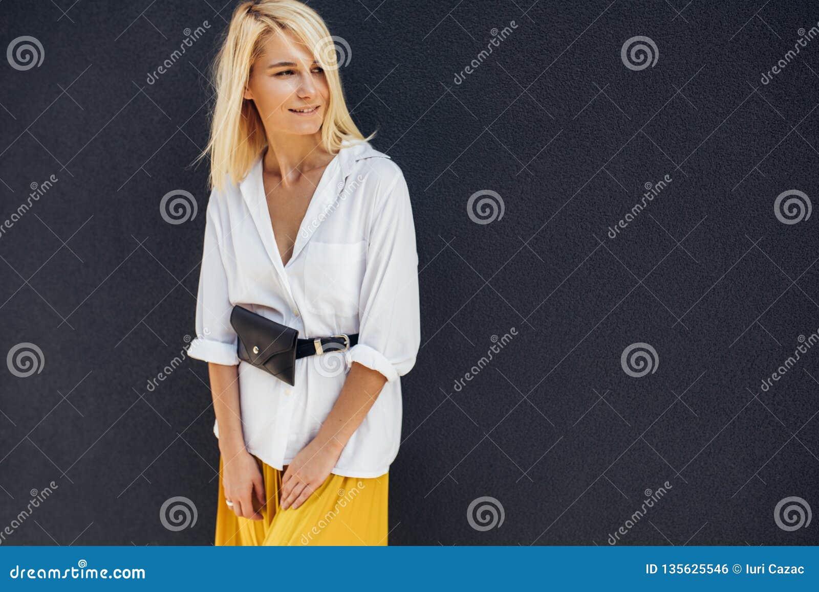 Tir horizontal de portrait de la femelle blonde assez jeune souriant et regardant un côté contre le mur gris sur la rue franc