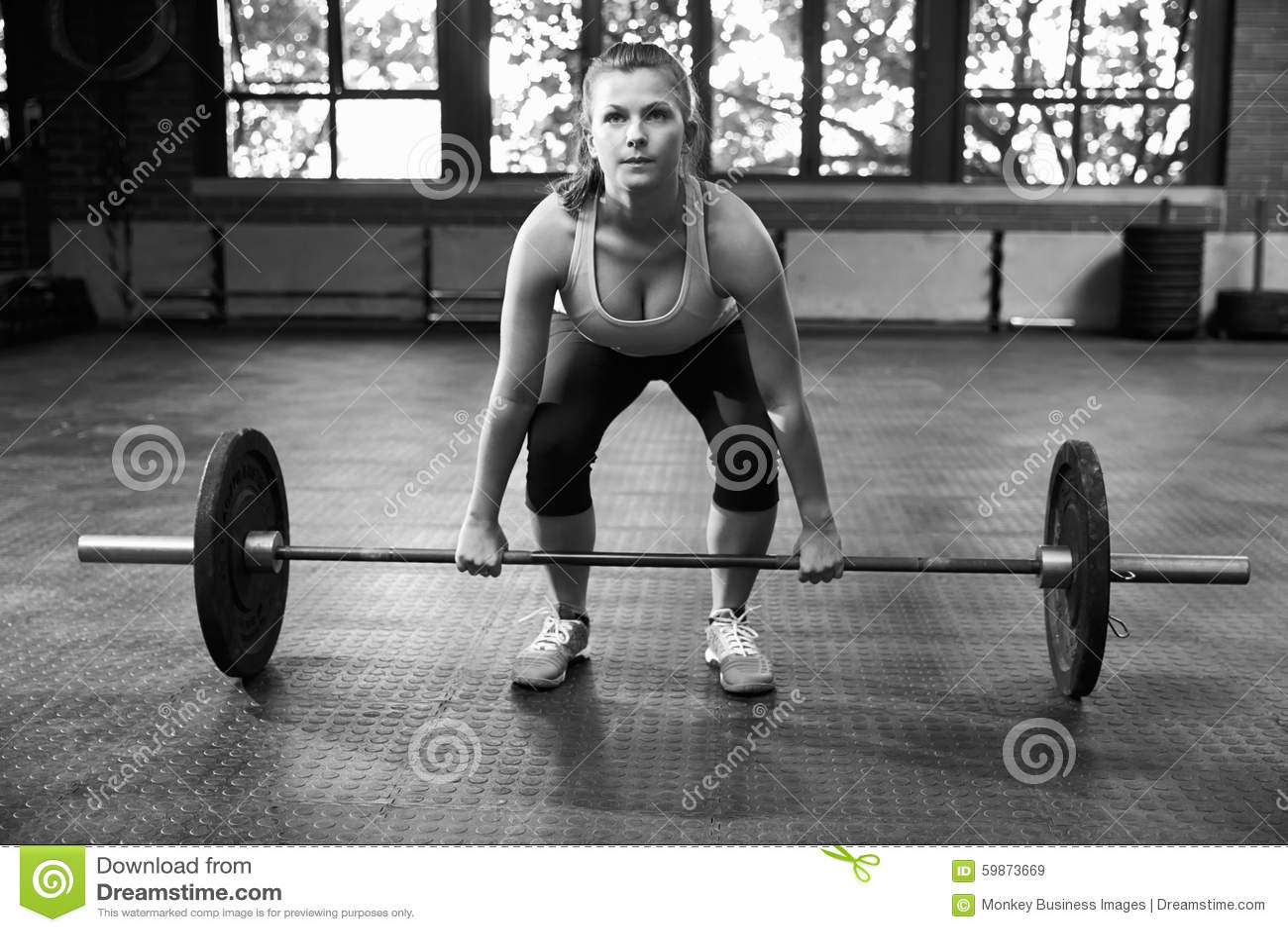 Tir noir et blanc de femme préparant pour soulever des poids
