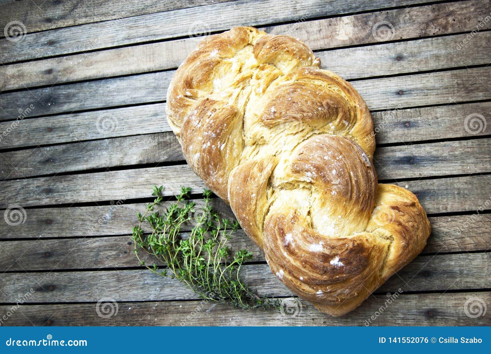 Tir supérieur, fin de pain tressé cuit au four frais de vegan fait maison sur un fond en bois et rustique de table, cuisson à la