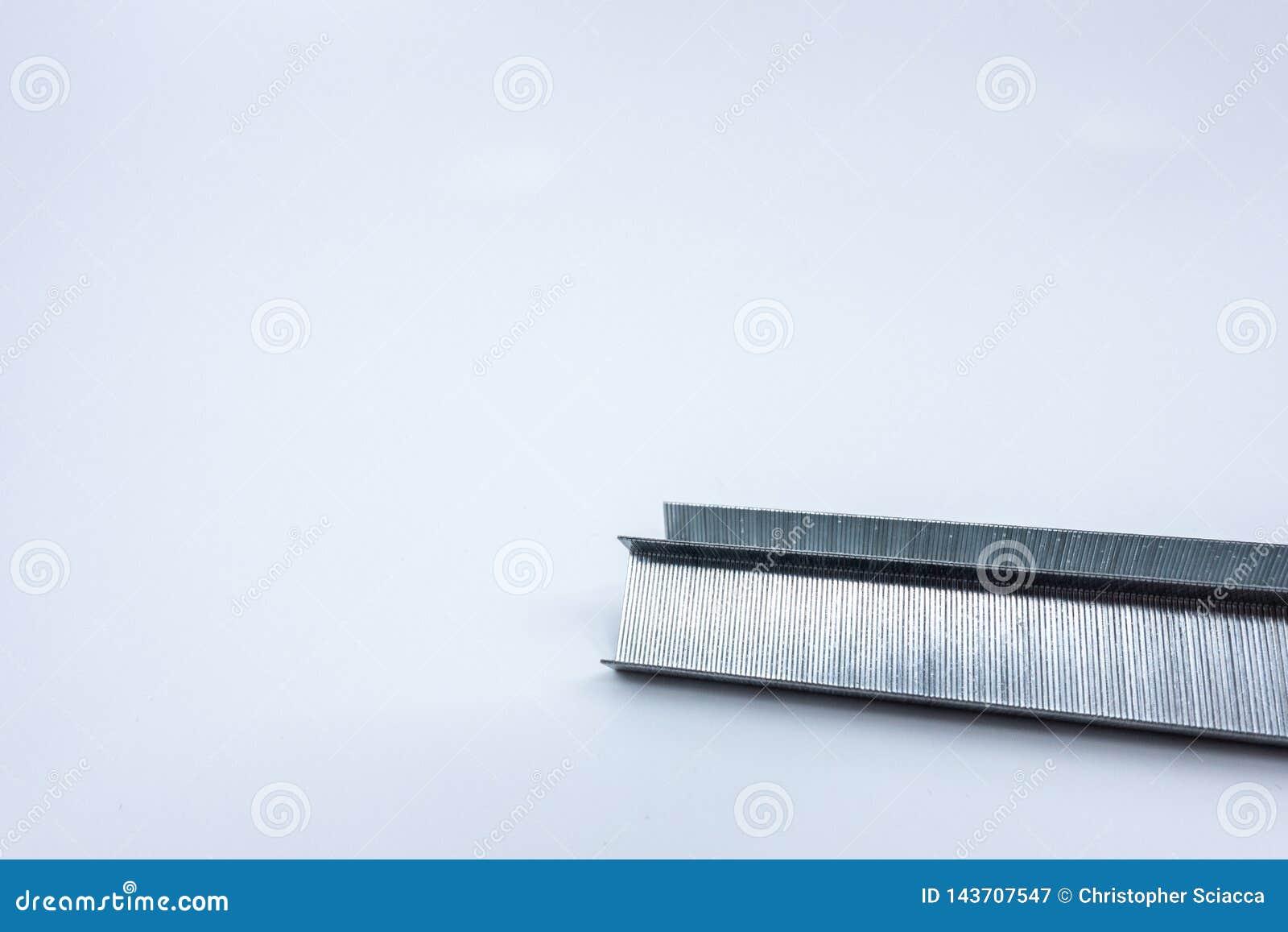 Tira de grapas aisladas contra un fondo blanco Materiales de oficina - imagen