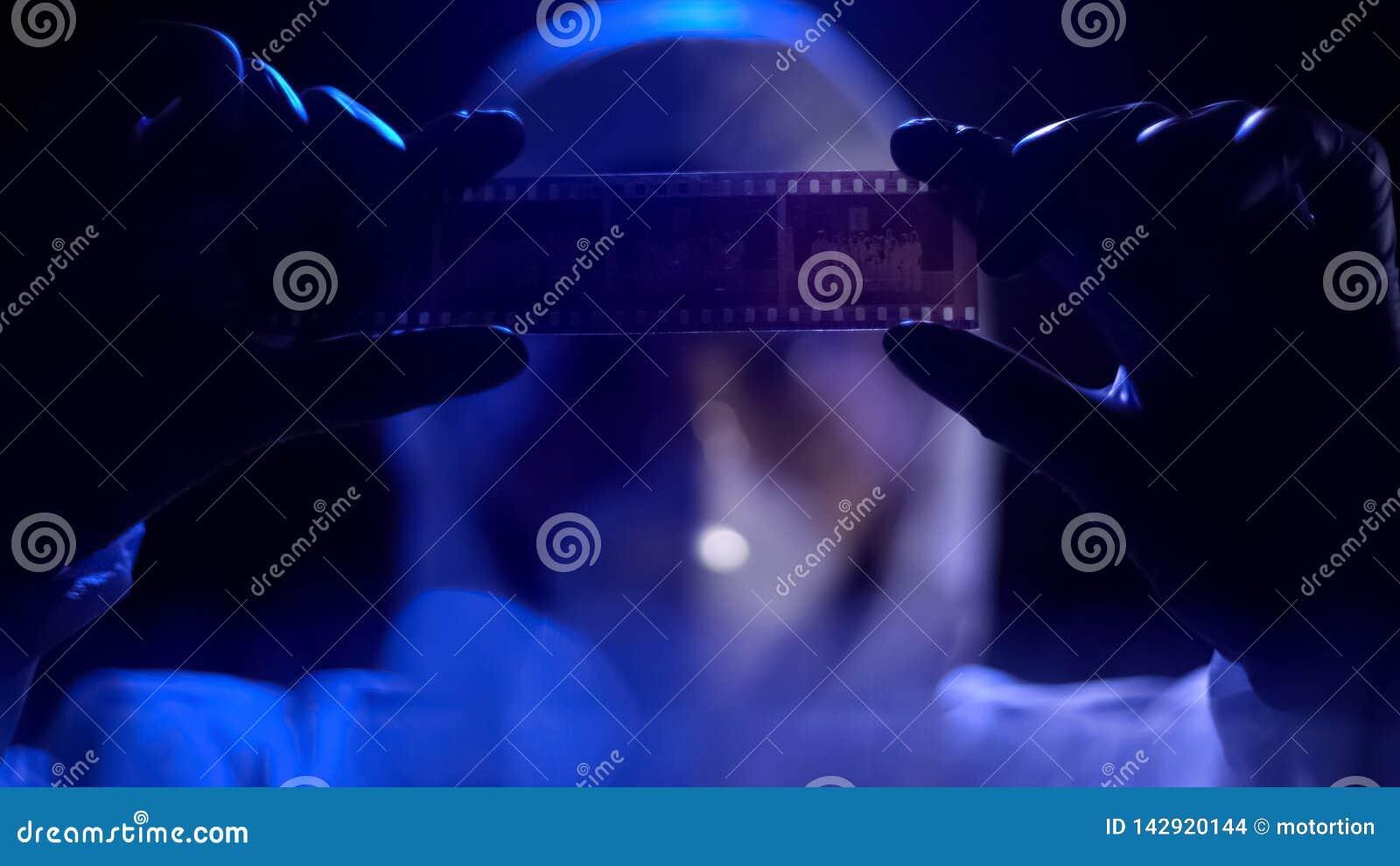Tira de película de observación del ayudante de laboratorio, buscando pruebas contra criminal