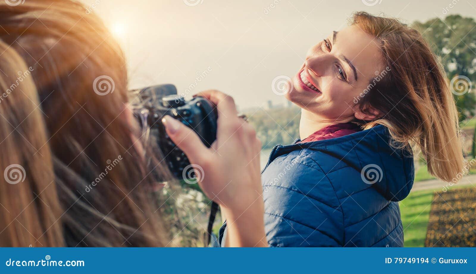 Tirado de un fotógrafo de la muchacha que toma una foto de un su amigo