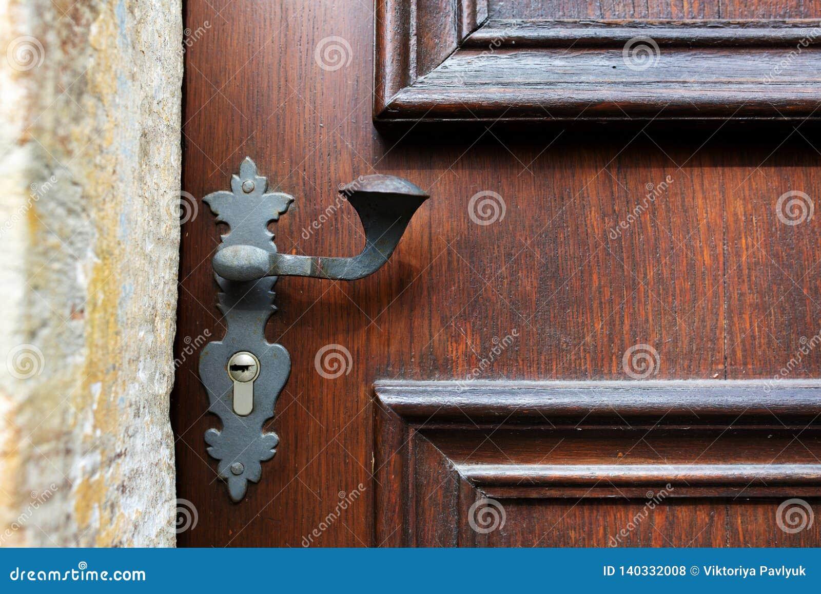 Tirador de puerta del vintage y ojo de la cerradura de una puerta tallada de madera Copie el espacio