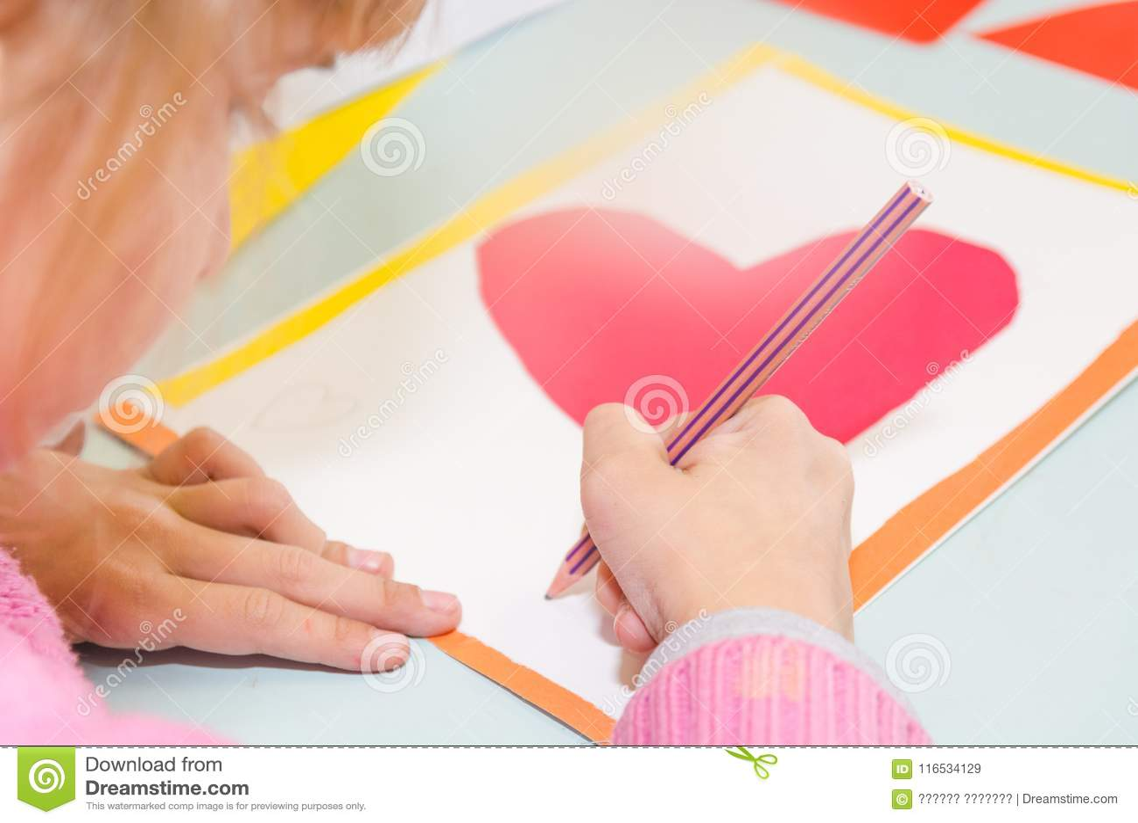 Tiraggio del bambino una cartolina I bambini sono impegnati in cucito La ragazza firma una cartolina il 14 febbraio