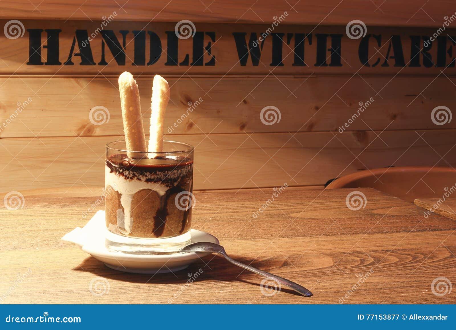 Tiramisu dans une tasse en verre Tiramisu dans le verre sur le fond en bois