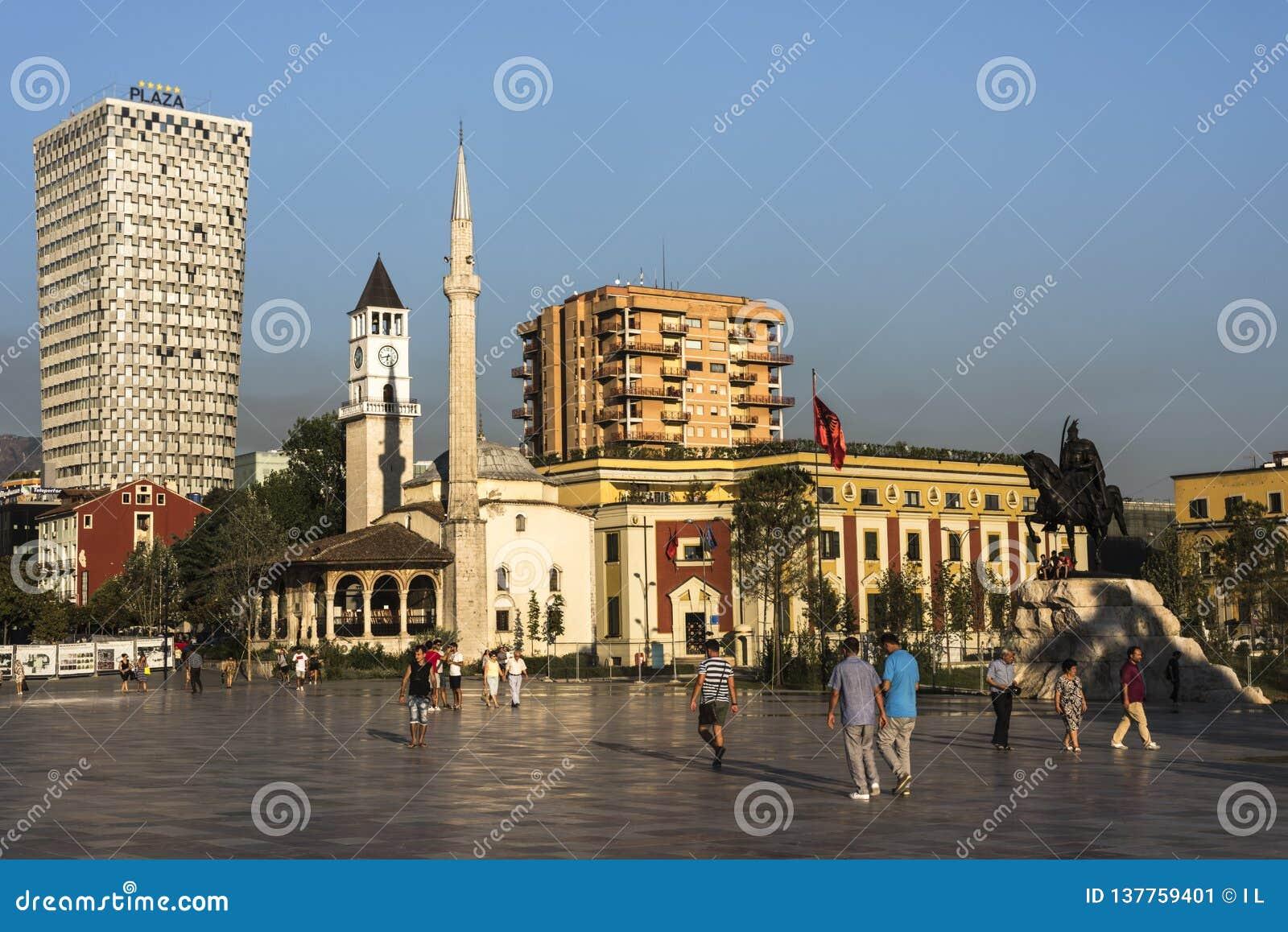 TIRANA, ALBANIEN - 1. AUGUST 2017: Einheimische an Skanderbeg-Quadrat am frühen Abend vor dem Piazza-Hotel und 'Rand Bey Mosque