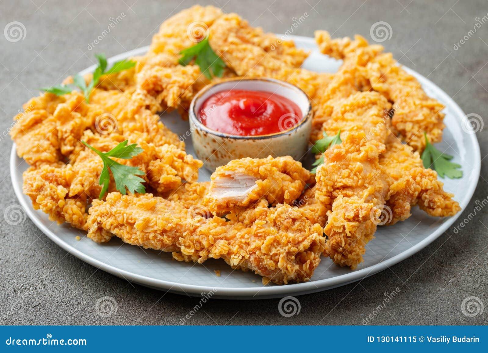 Tiras empanadas del pollo con la salsa de tomate de tomate en una placa blanca Alimentos de preparación rápida en fondo marrón os