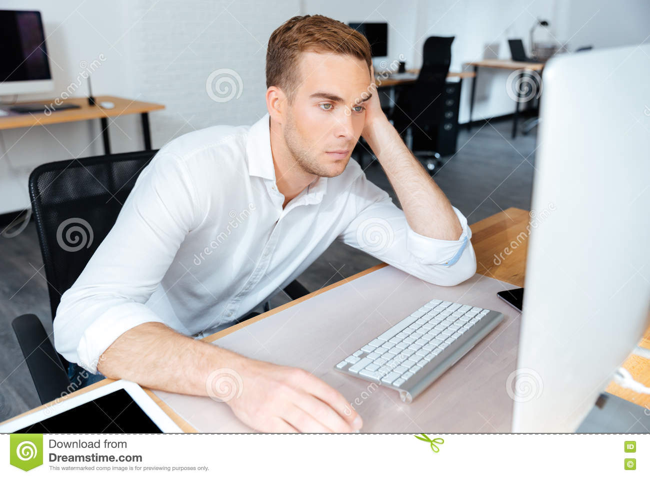tired bored young businessman working with computer in office stock