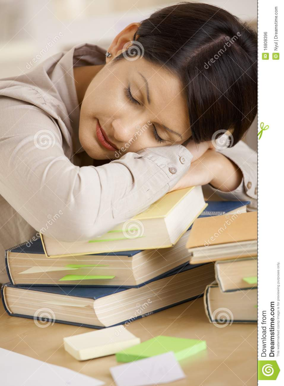 tired college student sleeping on pile of books royalty