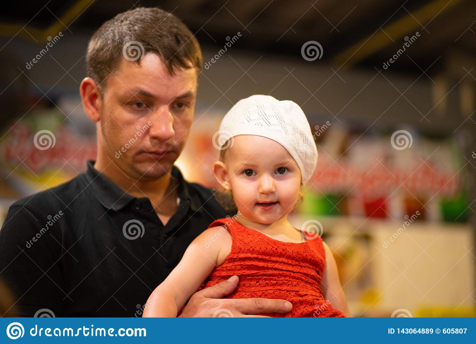 Tired dad holding daughter in his arms, fatherhood concept.