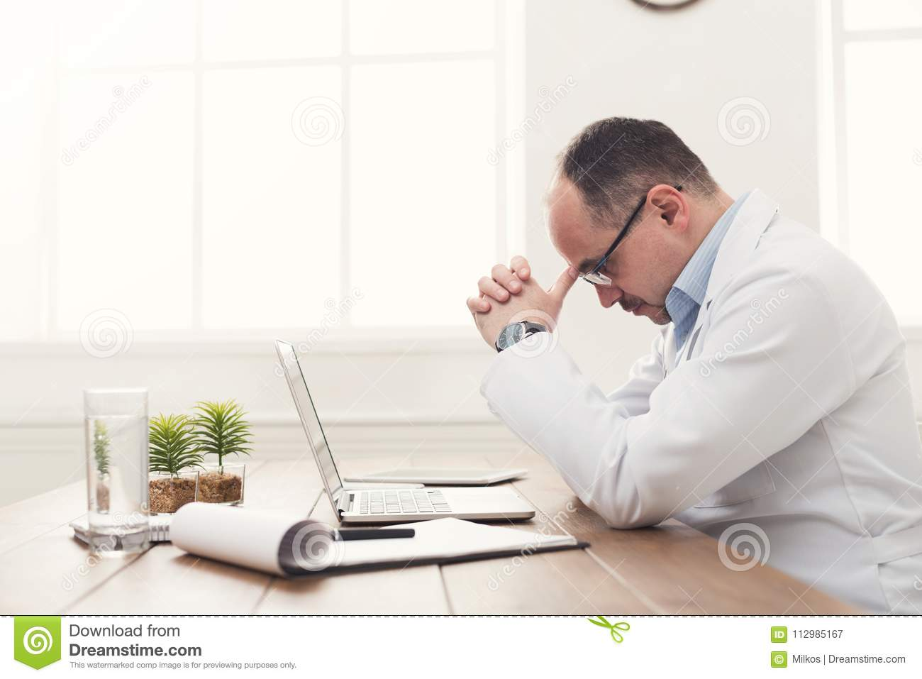 Tired doctor isitting at workplace in hospital