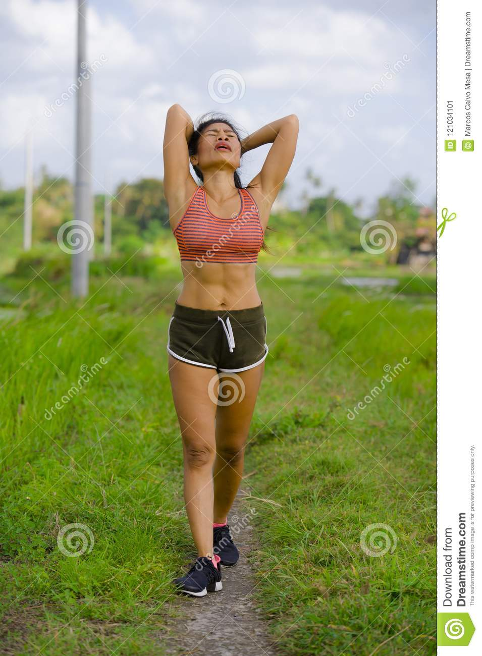 Tired and exhausted fit Asian sport woman training running workout at green field landscape background working hard in healthy lif