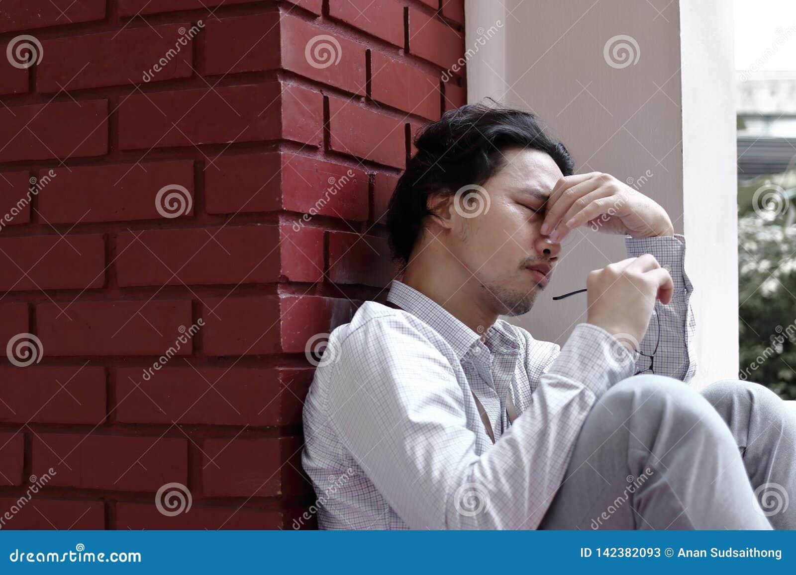 Tired forçou o sentimento asiático novo do homem de negócio decepcionado ou esgotado com trabalho no escritório exterior