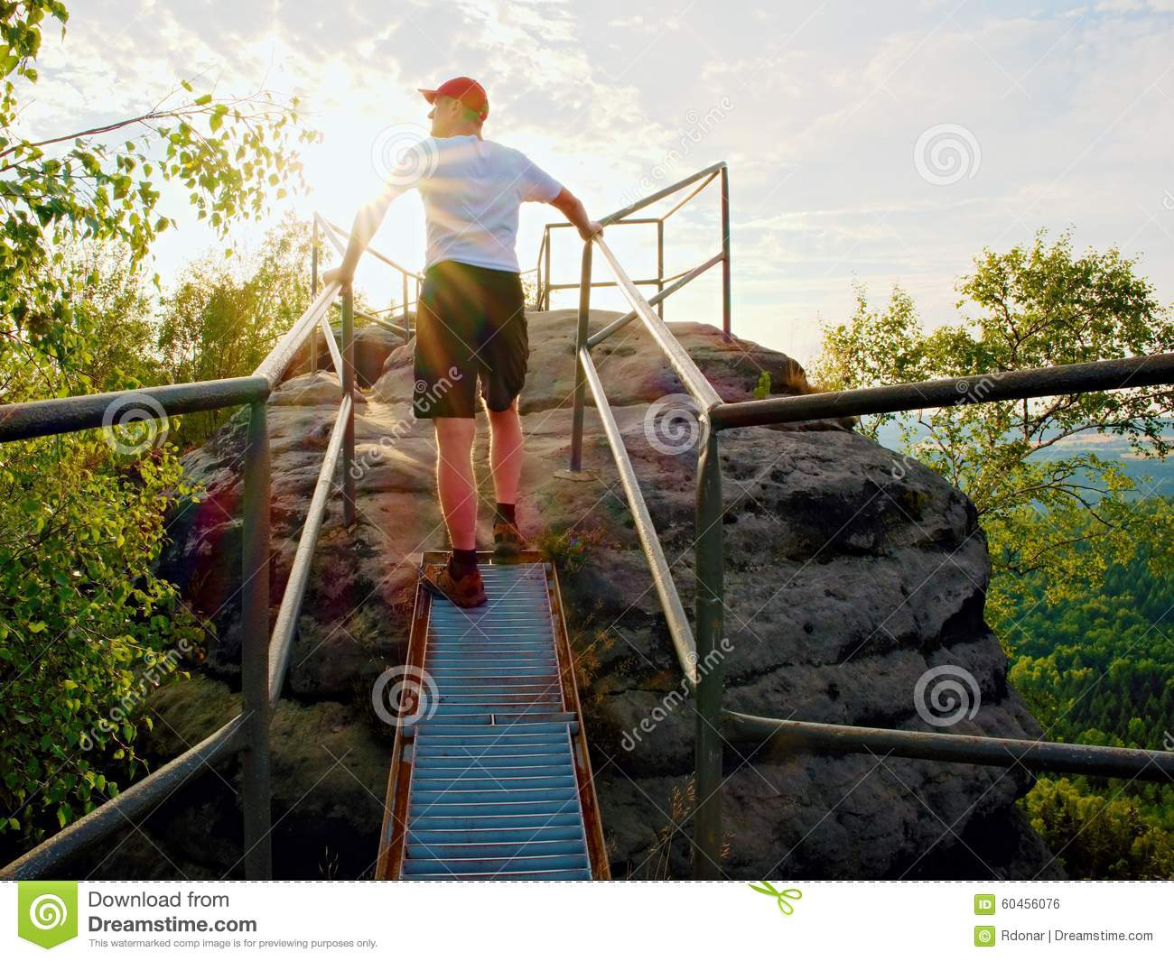 Tired hiker keep handrail on peak. Sunny spring daybreak in rocky mountains. Hiker with red baseball cap, dark pants and white shi