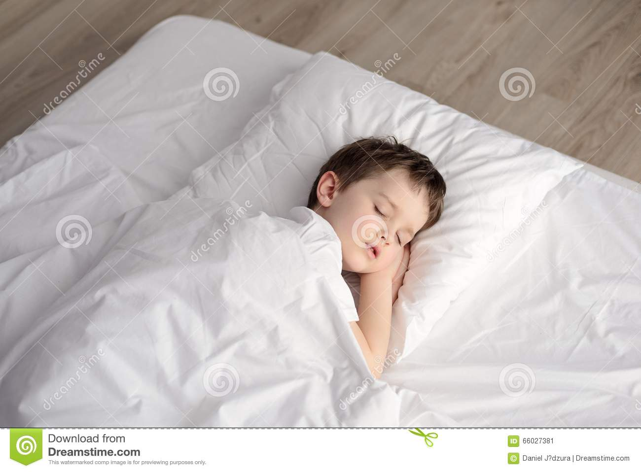 tired little boy sleeping in bed happy bedtime in white bedroom stock photo image 66027381. Black Bedroom Furniture Sets. Home Design Ideas