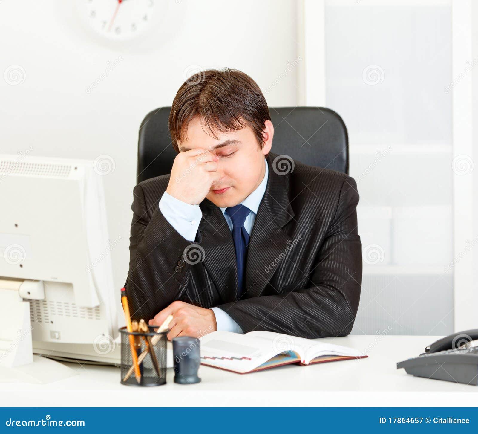 tired modern businessman sitting at office desk stock. Black Bedroom Furniture Sets. Home Design Ideas