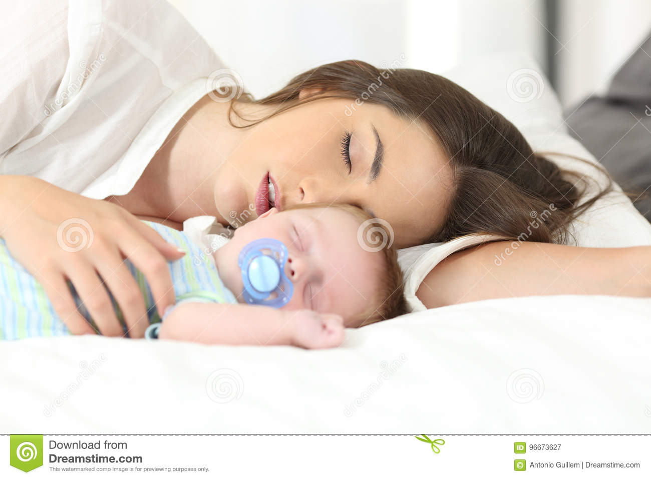 Tired mother sleeping with her baby