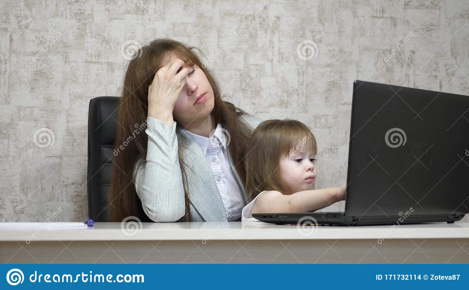 Tired Mother Works At The Table With Her Little Daughter