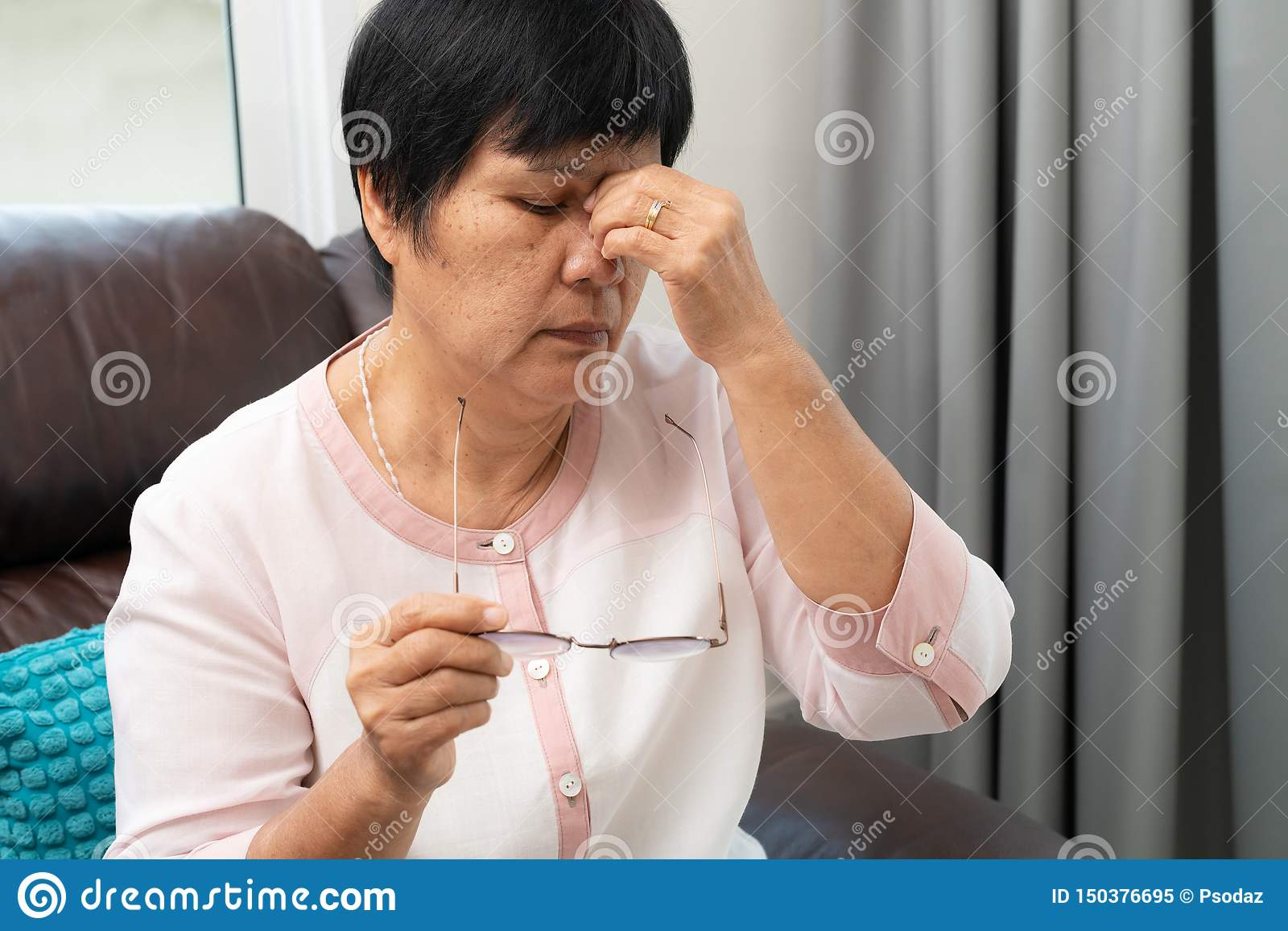 Tired old woman removing eyeglasses, massaging eyes after reading paper book. feeling discomfort because of long wearing glasses,
