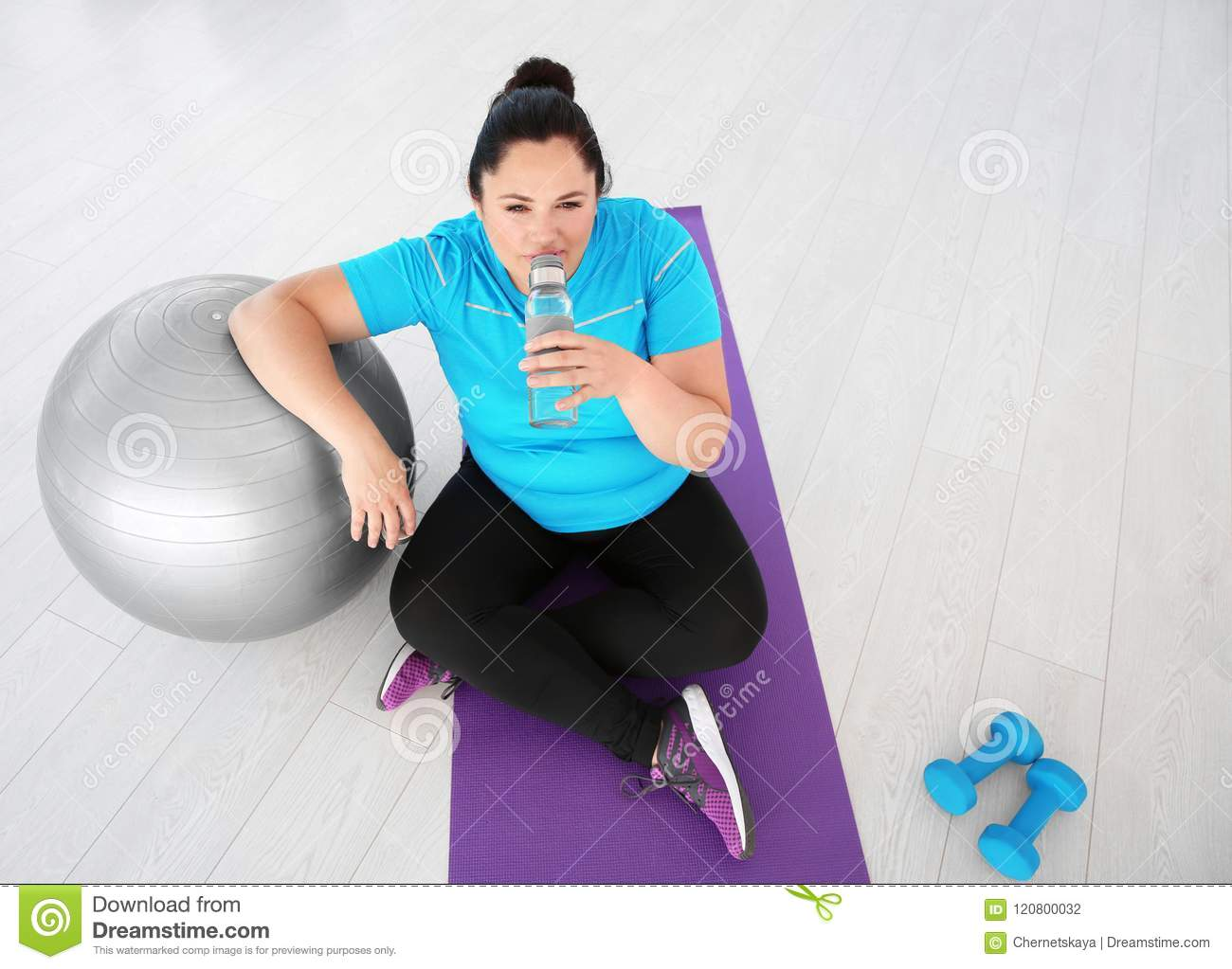 Tired overweight woman drinking water stock photo image of home