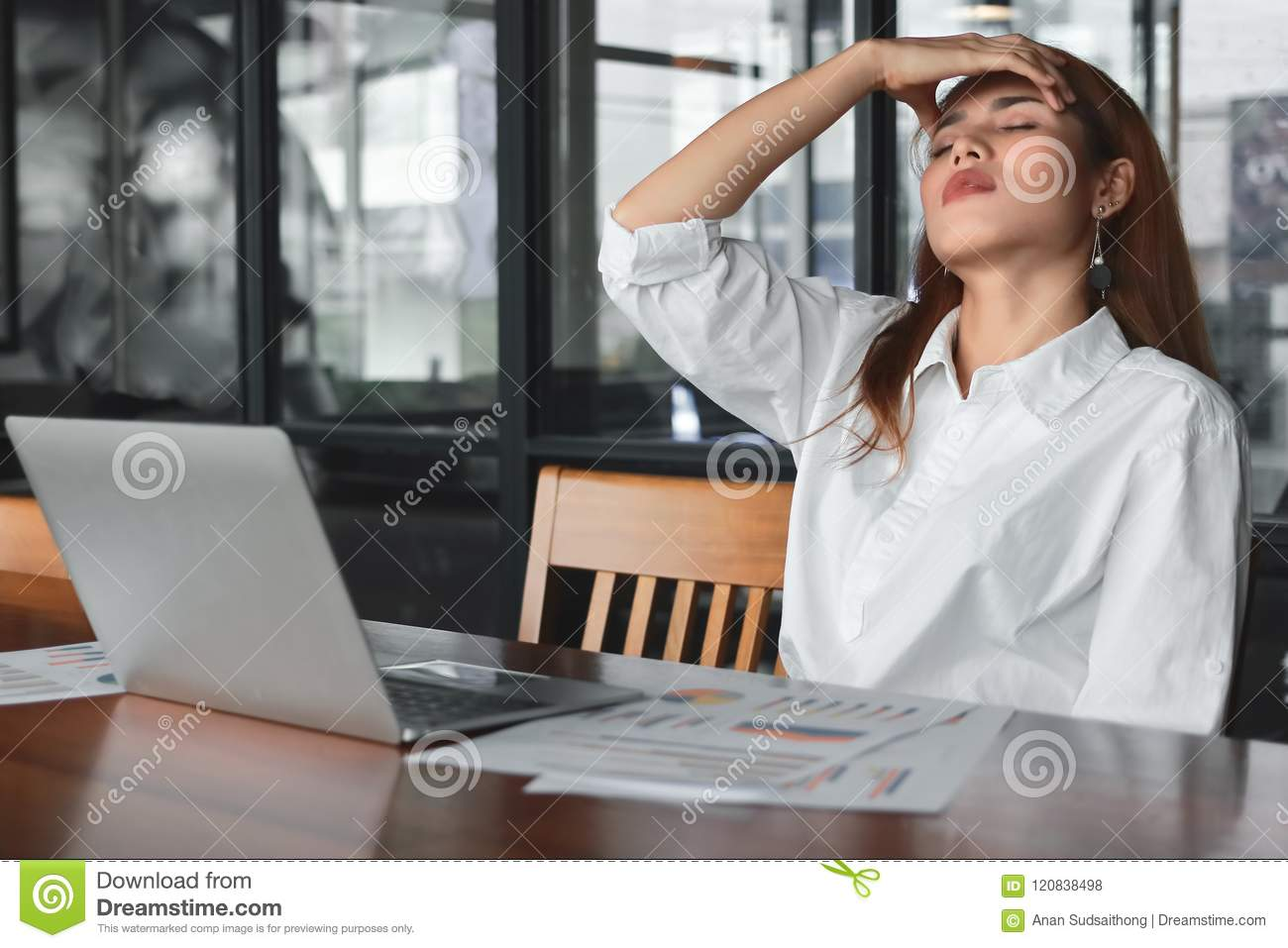 Tired overworked young Asian business woman suffering from severe depression in workplace.