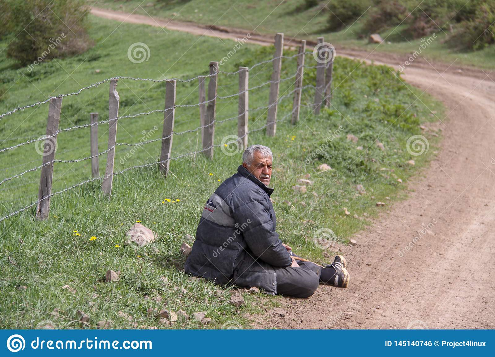 A tired rural man sitting next to the road on the floor, A farm is enclosed with a fence, Iran, Gilan