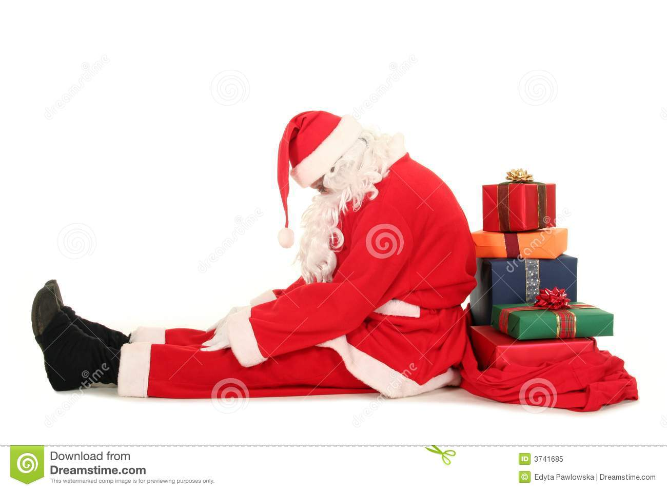Santa Claus sitting on floor with bag of Christmas presents.