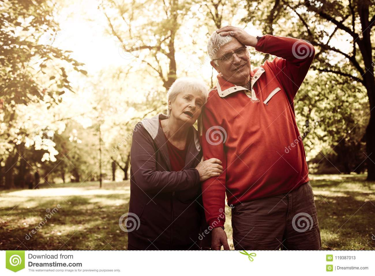 Tired senior couple standing in park after exercise.