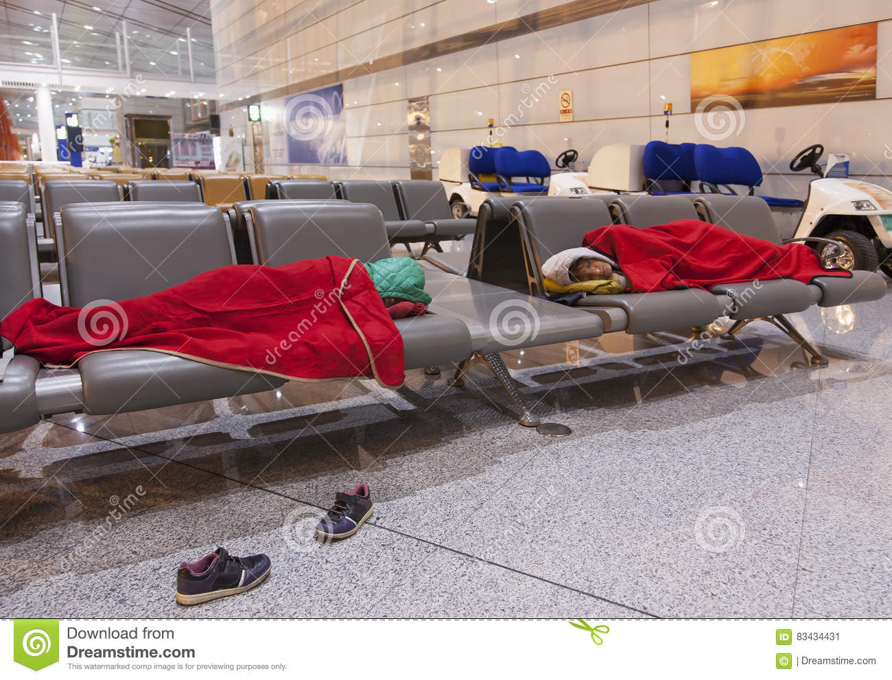 Tired travelers sleeping on the airpot departure gates bench
