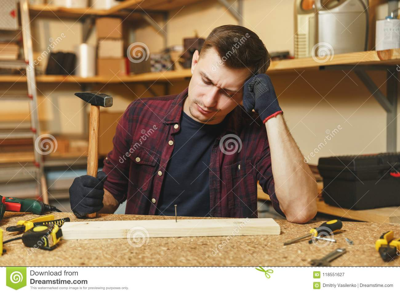 06c36801 Tired upset sad caucasian young man in plaid shirt, black T-shirt, gloves  hammering nails with hammer, working in carpentry workshop at wooden table  place ...