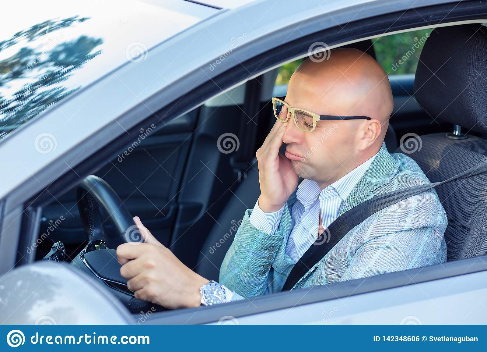 Sleepy fatigued yawning exhausted young man driving his car