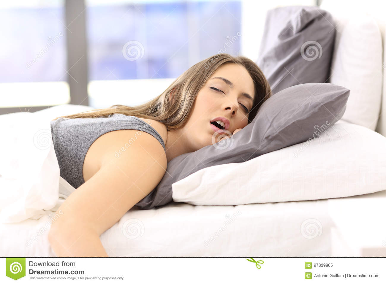 Tired woman resting on a bed at home