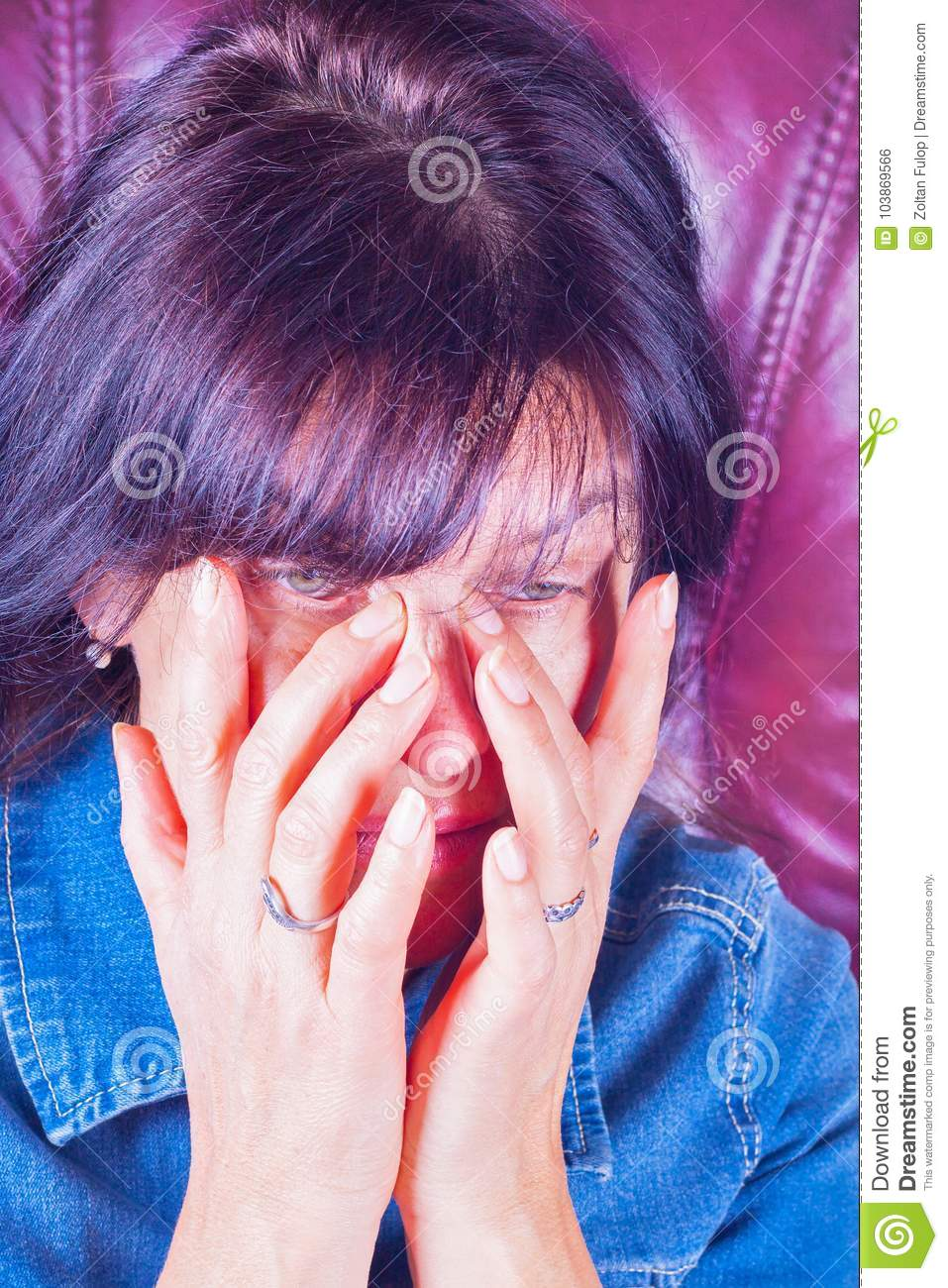 A tired woman rubbing her eyes.