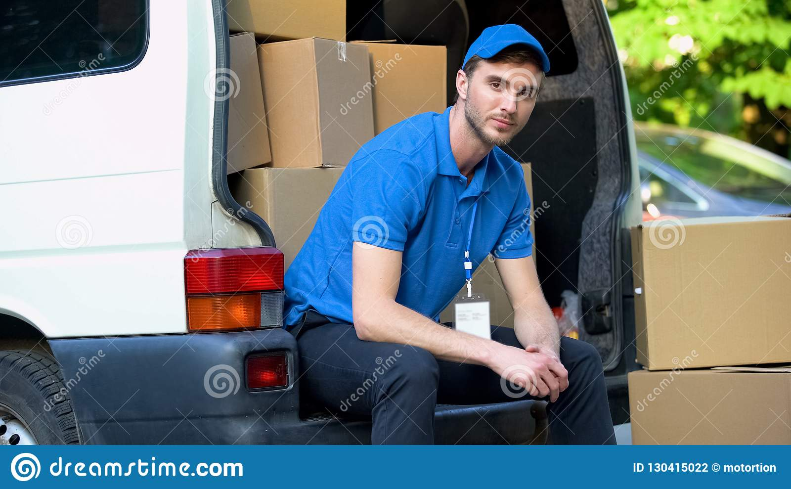 Tired worker of moving company resting, sitting in van full of cardboard boxes